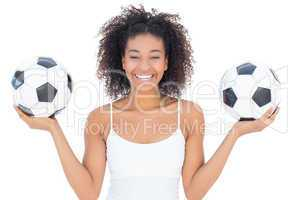 Pretty girl with afro hairstyle smiling at camera holding footba