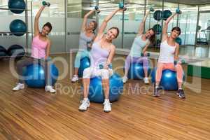 Fitness class holding dumbbells on exercise balls in studio