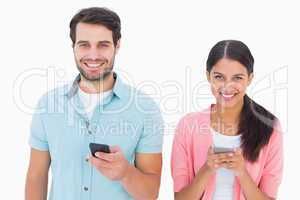 Happy couple sending text messages