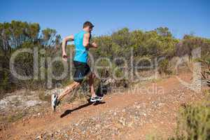 Athletic man jogging up country trail