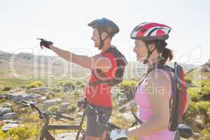 Fit cyclist couple looking ahead on mountain trail