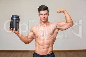 Muscular man posing with nutritional supplement in gym