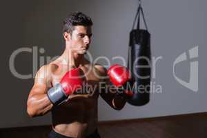 Shirtless muscular boxer in defensive stance in health club