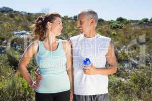 Active couple embracing each other on a jog in the country