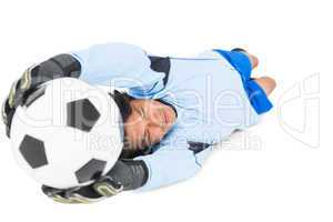 Goalkeeper in blue saving ball