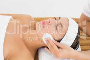 Hand cleaning womans face with cotton swab