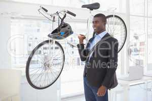 Happy businessman carrying his bicycle