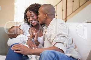 Happy parents spending time with baby on the couch
