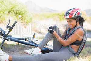 Fit woman holding her injured knee after bike crash