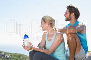 Fit couple taking a break at summit looking at the view