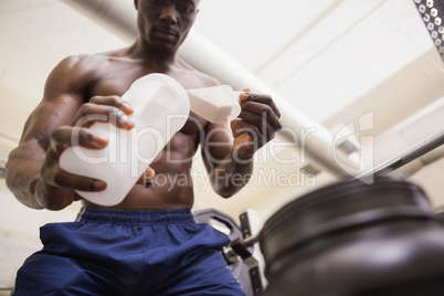 Body builder scooping up protein powder
