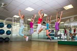 Fitness class jumping up in studio