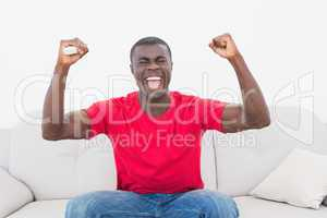 Cheering football fan in red sitting on couch