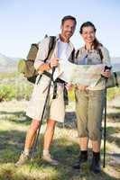 Hiking couple consulting the map in the countryside