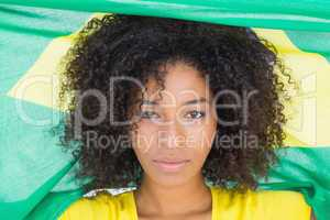 Pretty girl in yellow tshirt holding brazilian flag looking at c