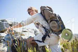 Handsome hiker hiking through rough terrain