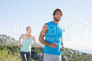 Fit couple jogging through countryside