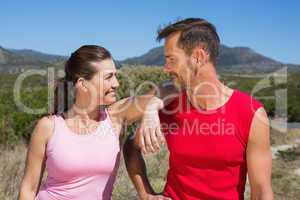 Active couple standing on country terrain smiling at each other