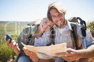Hiking couple taking a break on mountain terrain using map and c