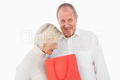 Older couple holding red gift bag