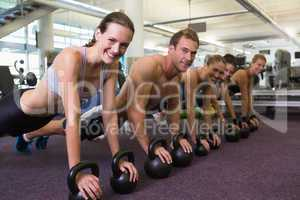 Fitness class in plank position with kettlebells