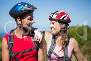 Active couple cycling in the countryside smiling at each other