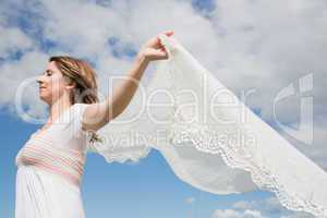 Woman holding out scarf against blue sky and clouds