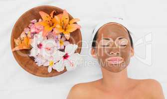 Smiling brunette getting a mud treatment facial beside bowl of f