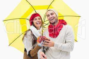 Attractive young couple in warm clothes holding umbrella and lea