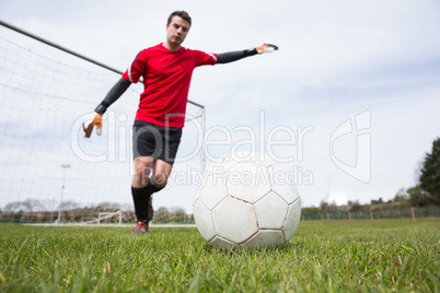 Goalkeeper in red kicking ball away from goal