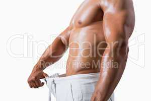 Mid section of a muscular man in an over sized pants