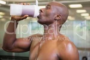 Sporty man drinking protein in gym