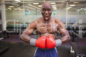 Muscular boxer flexing muscles in health club