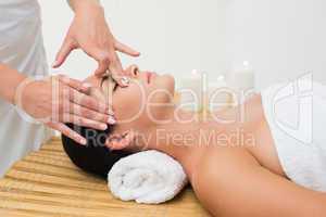 Peaceful brunette enjoying a facial massage
