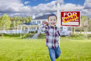 Boy Playing Ball in Yard Near Sold Real Estate Sign