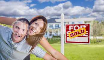 Military Couple In Front of Home with Sold Sign
