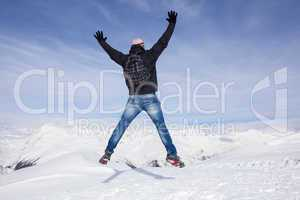 Young man jumps for joy in the snowy mountains
