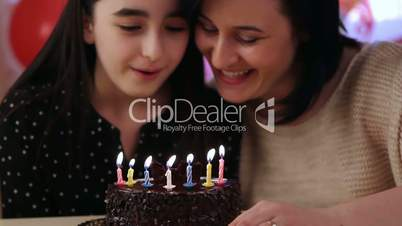 Mother and daughter blowing candles on birthday cake
