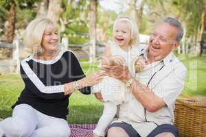 Affectionate Granddaughter and Grandparents Playing At The Park