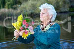 Seniorin collects colorful autumn leaves
