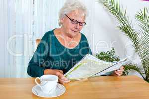 Elderly woman reading a magazine