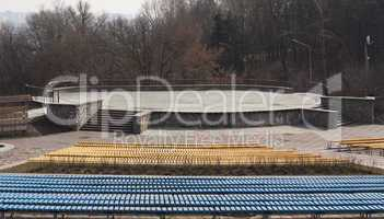 Row of wooden seats on a spectator grandstand photo. Bench in the park for the show
