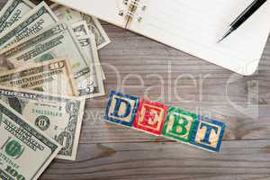 Banknotes and debt word.
