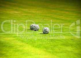 Soccer balls on the green field
