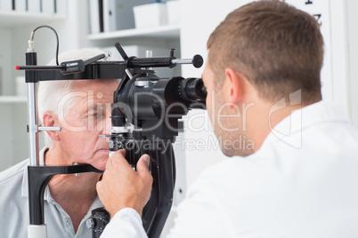 Optician examining senior patients eyes through slit lamp