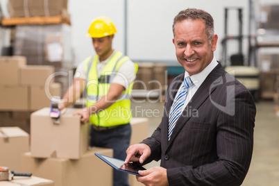Boss using digital tablet in warehouse