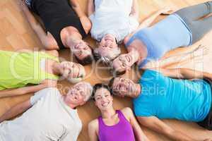 Happy people lying on hardwood floor at gym