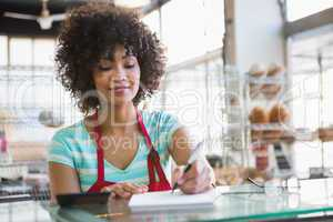 Smiling waitress writing on notepad