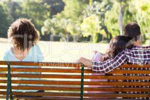 Lonely woman sitting with couple in park