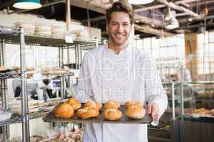 Cheerful baker holding tray of bread